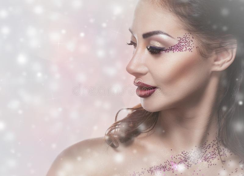 Una mujer joven con maquillaje creativo y el peinado hermoso, en el fondo de copos de nieve imagenes de archivo