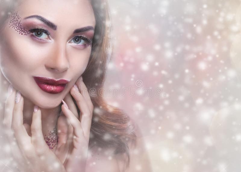 Una mujer joven con maquillaje creativo y el peinado hermoso, en el fondo de copos de nieve imagen de archivo libre de regalías