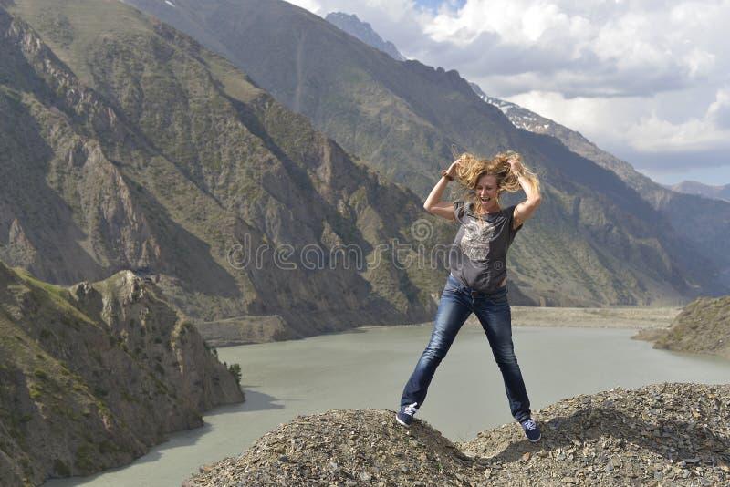Una mujer joven con risas lanudas del pelo mientras que se coloca al borde de un acantilado sobre un lago fotos de archivo