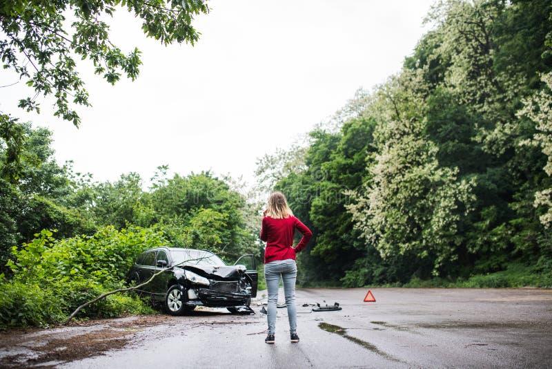 Una mujer joven con smartphone por el coche dañado después de un accidente de tráfico, haciendo una llamada de teléfono fotografía de archivo libre de regalías