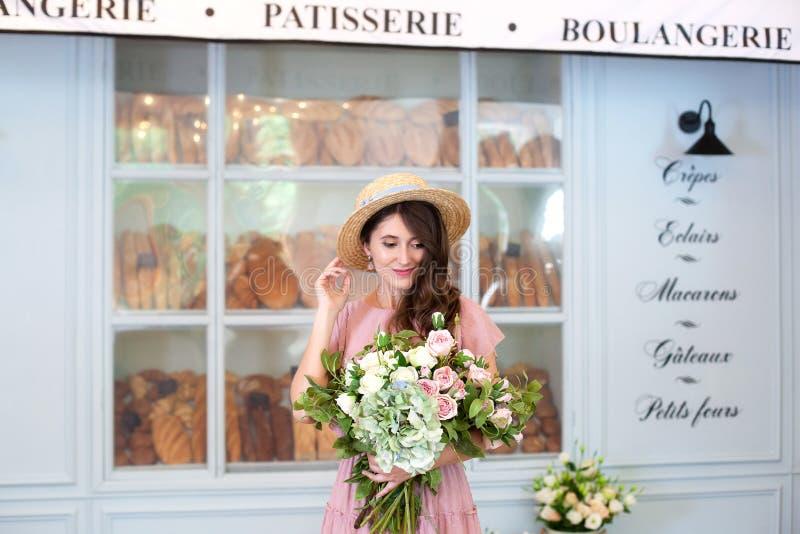 Una mujer joven con una sonrisa se coloca cerca de la ventana de la tienda en un vestido y con un ramo de flores Pasteles en un f imágenes de archivo libres de regalías