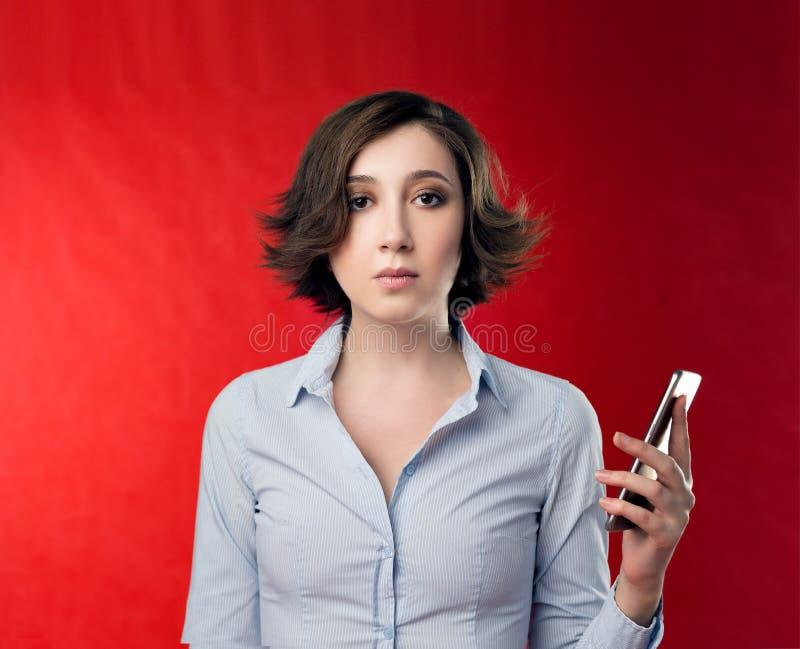 Una mujer joven con un corte de pelo corto en una blusa azul de la oficina en un fondo rojo que sostiene un teléfono a disposició imagen de archivo libre de regalías