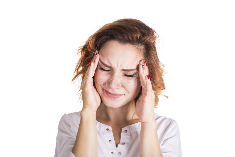 Una mujer joven con un dolor de cabeza que lleva a cabo la cabeza, aislada en el fondo blanco Concepto del dolor de cabeza imagen de archivo