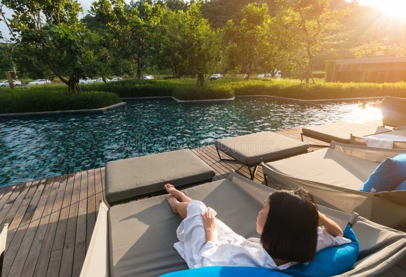 Una mujer joven del pelo corto está descansando en la cama de la piscina fotos de archivo libres de regalías