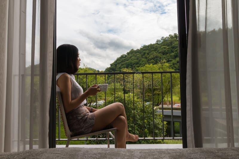 Una mujer joven del pelo corto que se sienta en el balcón imagen de archivo libre de regalías