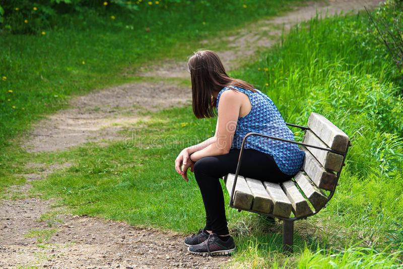 Una mujer joven descansa sobre un banco como vientos de un rastro alrededor de ella fotos de archivo