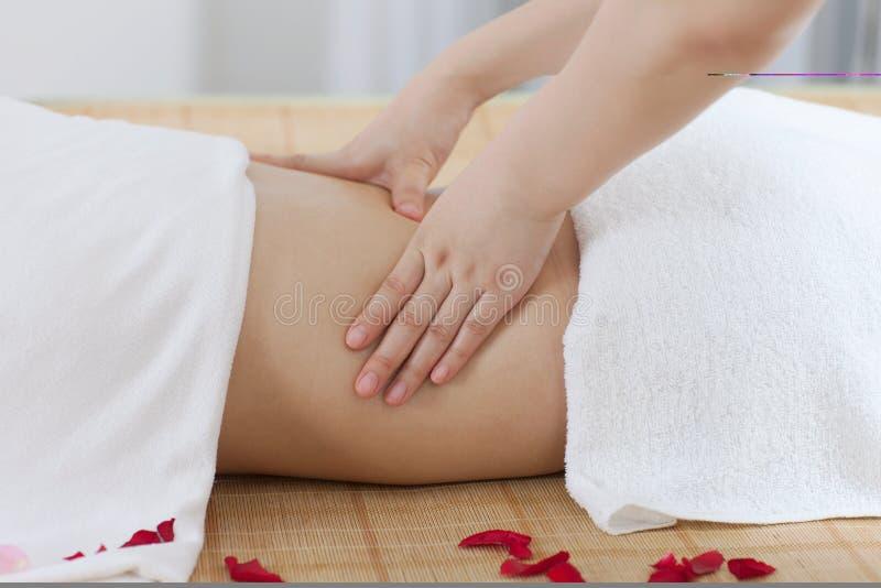 Una mujer joven disfruta de masaje en el balneario foto de archivo libre de regalías