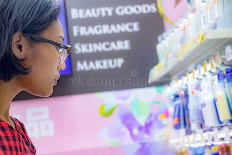 Una mujer joven elige los cosméticos en una tienda fotografía de archivo