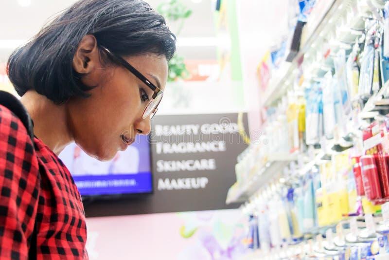 Una mujer joven elige los cosm?ticos en una tienda fotografía de archivo