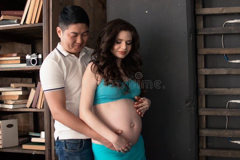 Una mujer joven embarazada y un hombre se están colocando de lado a lado, fotografía de archivo