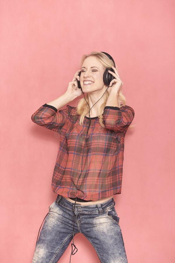 Una mujer joven, emoci?n de risa hilarante, el escuchar hilarante la m?sica en los auriculares fotografía de archivo libre de regalías