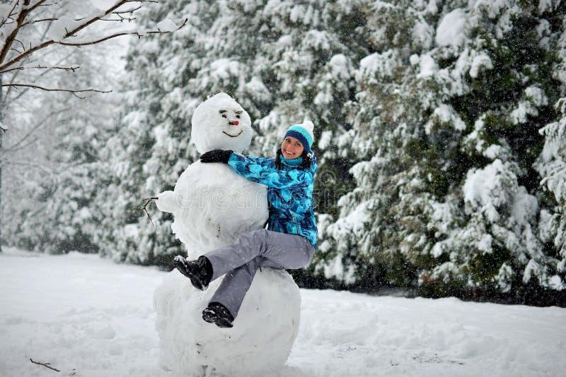 Una mujer joven en el bosque en invierno abraza un muñeco de nieve grande imágenes de archivo libres de regalías
