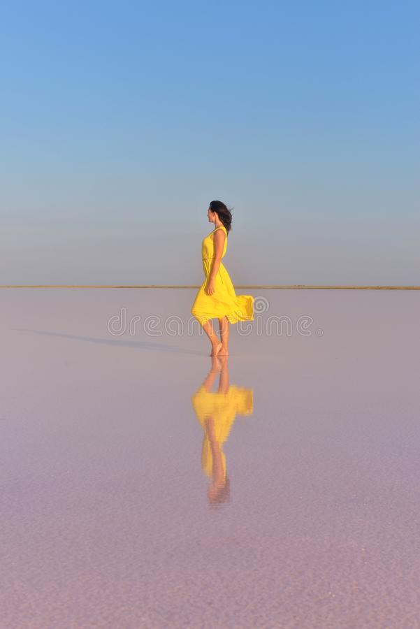 Una mujer joven en el medio de un lago de sal rosado se coloca en un vestido amarillo brillante y resuelve la puesta del sol fotografía de archivo libre de regalías