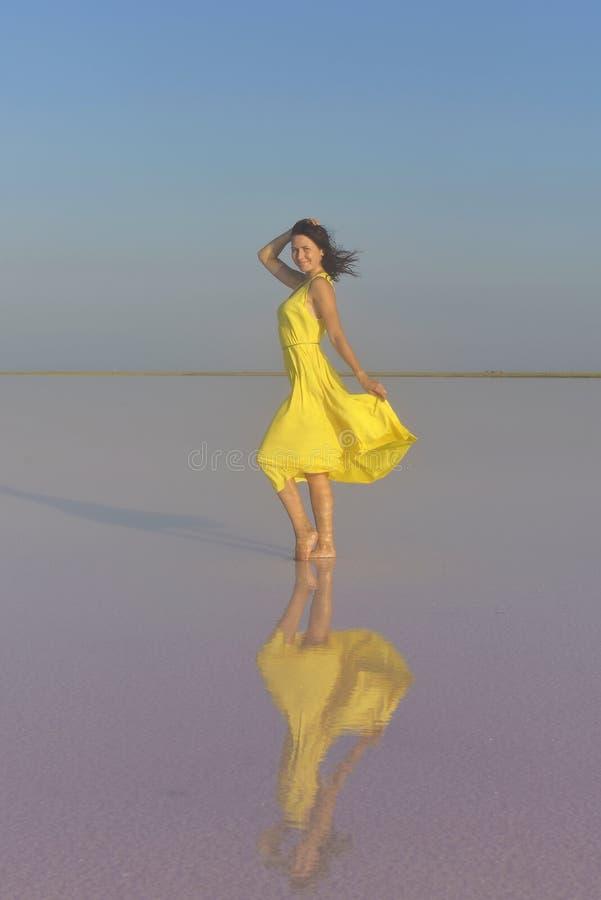 Una mujer joven en el medio de un lago de sal rosado se coloca en un vestido amarillo brillante y resuelve la puesta del sol imágenes de archivo libres de regalías