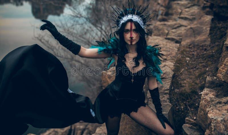 Una mujer joven en la imagen de una hada y una situación de la bruja al lado de rocas sobre un lago foto de archivo libre de regalías