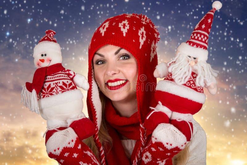 Una mujer joven en ropa hecha punto hermosa está sosteniendo un juguete de la Navidad con un muñeco de nieve y Santa Claus fotos de archivo libres de regalías