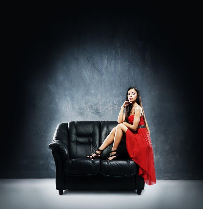 Una mujer joven en un vestido rojo en un sofá de cuero negro fotografía de archivo