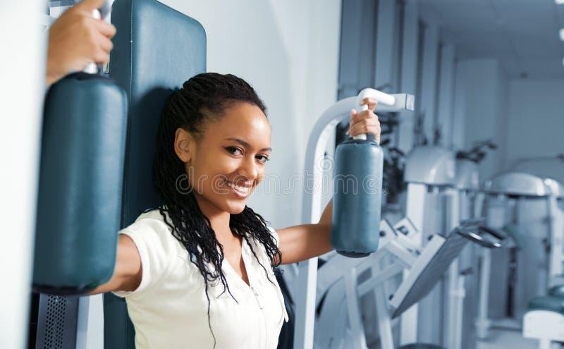 Una mujer joven en una gimnasia fotos de archivo
