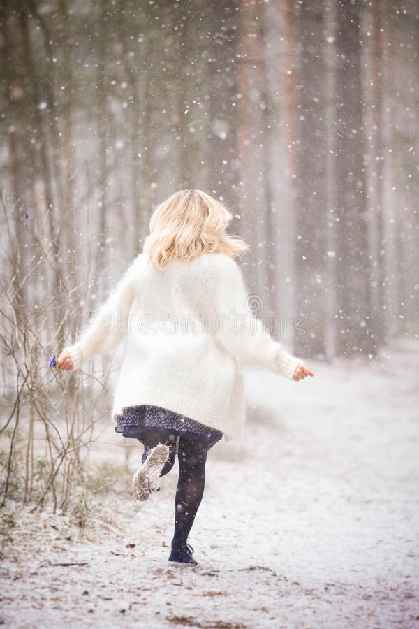 Una mujer joven en una rebeca caliente blanca que corre en un bosque y que sostiene un manojo de primeras flores del azul de la p fotografía de archivo
