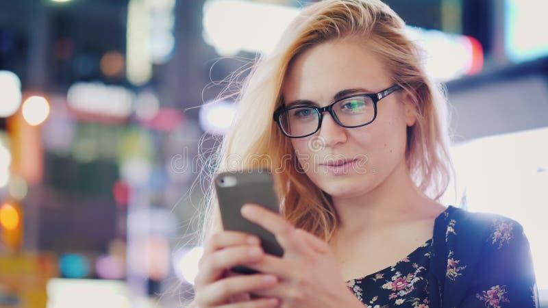 Una mujer joven en vidrios utiliza un smartphone en una ciudad de la noche Contra la perspectiva de las luces borrosas de la noch imagen de archivo