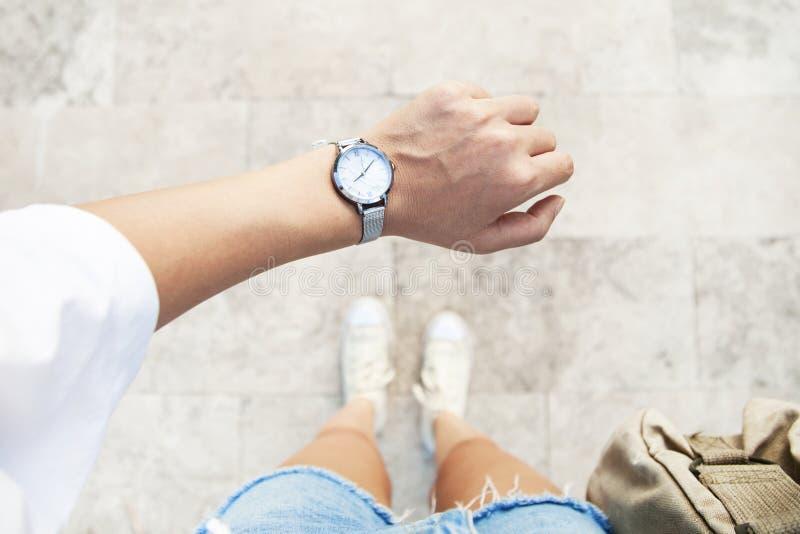 Una mujer joven es atrasada a tiempo, a toda prisa ella comprueba el plazo en su reloj clásico fotografía de archivo