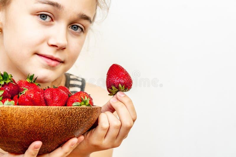 Una mujer joven est? sosteniendo un cuenco de fresas imágenes de archivo libres de regalías