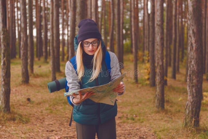 Una mujer joven hermosa con el mapa del viaje y mochila en bosque del pino fotografía de archivo