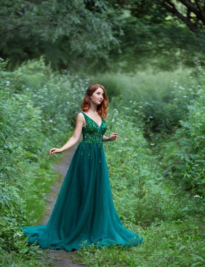 Una mujer joven hermosa con un pelo rojo Un vestido gorgerous con un penacho largo imágenes de archivo libres de regalías