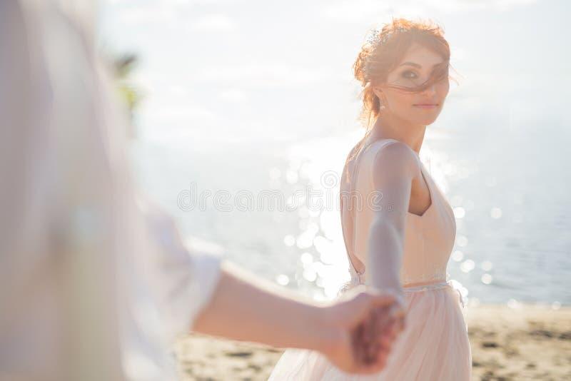 Una mujer joven hermosa, controles la mano del hombre en el aire abierto Sígame La neblina se crea para el marco romántico fotografía de archivo