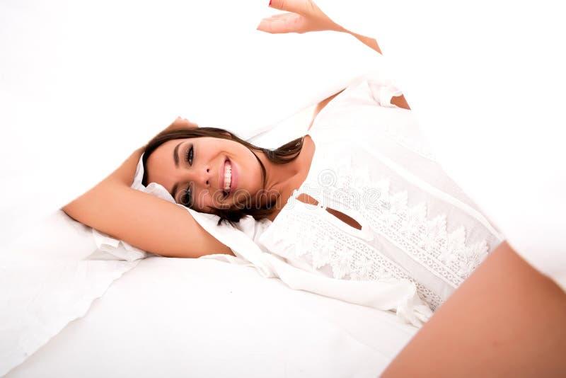 Una mujer joven hermosa debajo de las hojas en la cama imagen de archivo