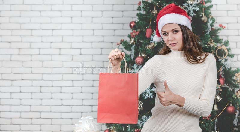 Una mujer joven hermosa del caucasion que lleva a cabo el bolso que hace compras rojo y t foto de archivo