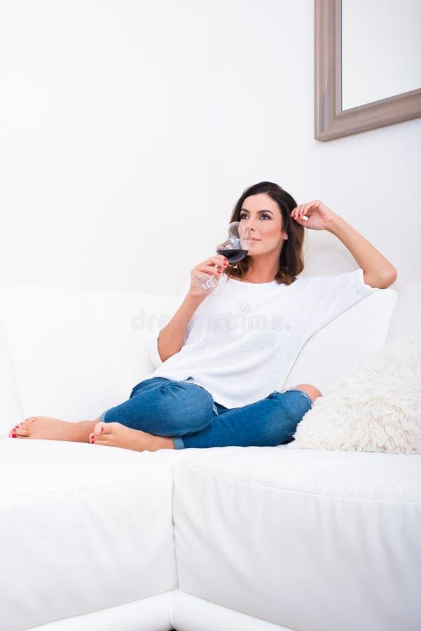 Una mujer joven hermosa en el sofá imagenes de archivo
