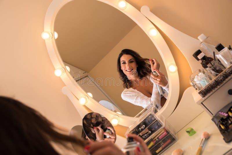 Una mujer joven hermosa en una tabla del maquillaje imagen de archivo libre de regalías
