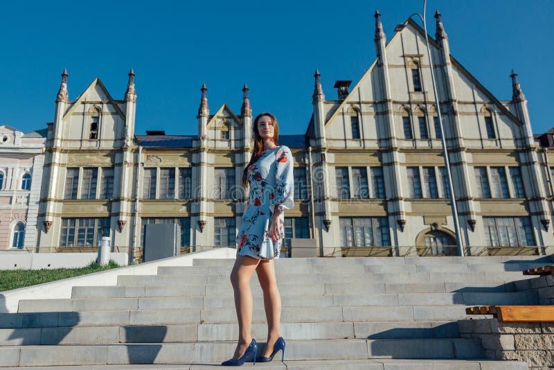 Una mujer joven hermosa en un vestido azul delicado imagen de archivo