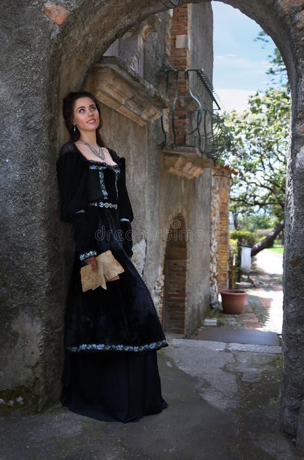 Una mujer joven hermosa en un vestido medieval con una letra en sus manos fotos de archivo