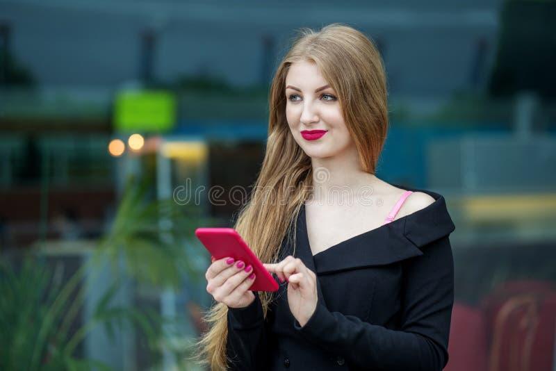 Una mujer joven hermosa está hojeando el email El concepto de Internet, de la tecnología, del negocio, de la comunicación y de la imagen de archivo