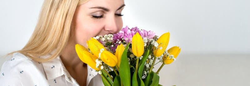 Una mujer joven hermosa inhala el aroma de un ramo de la primavera foto de archivo
