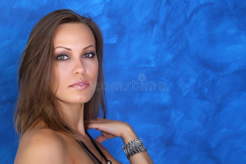 Una mujer joven hermosa lleva a cabo una mano cerca del cuello imagen de archivo libre de regalías