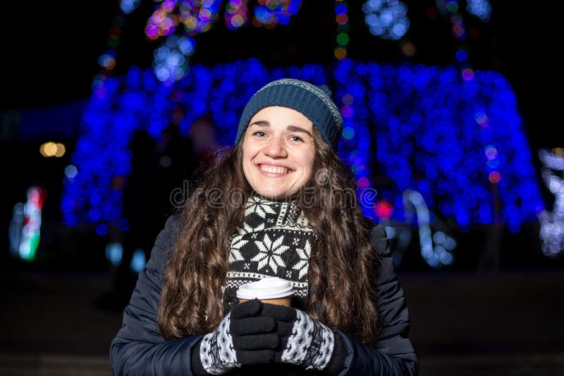 Una mujer joven hermosa que goza de una taza de café caliente en el mercado de la Navidad fotos de archivo