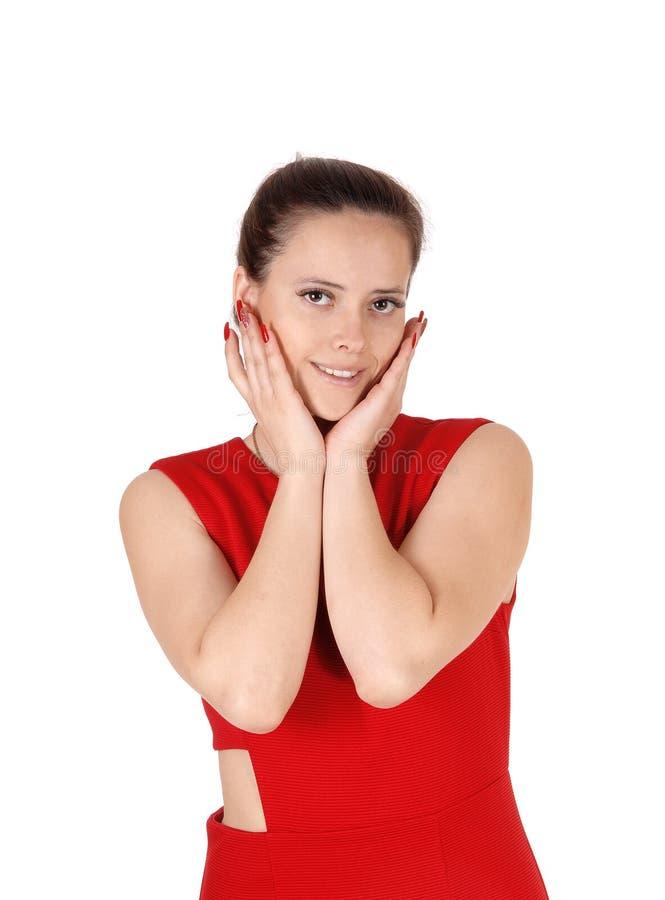 Una mujer joven hermosa que lleva a cabo ambas manos en su cara fotografía de archivo