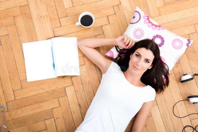 Una mujer joven hermosa que pone en el piso, con el gad electrónico fotos de archivo libres de regalías