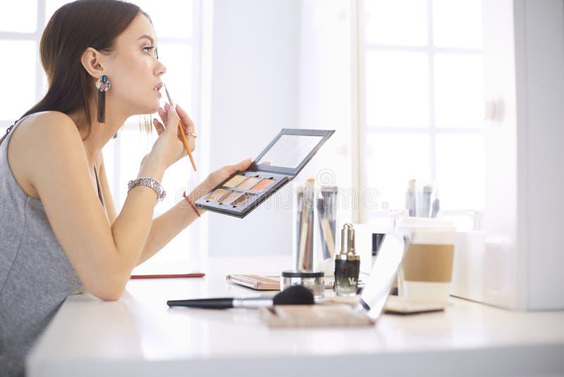 Una mujer joven hermosa que se sienta en una tabla del maquillaje y que hace su maquillaje fotografía de archivo