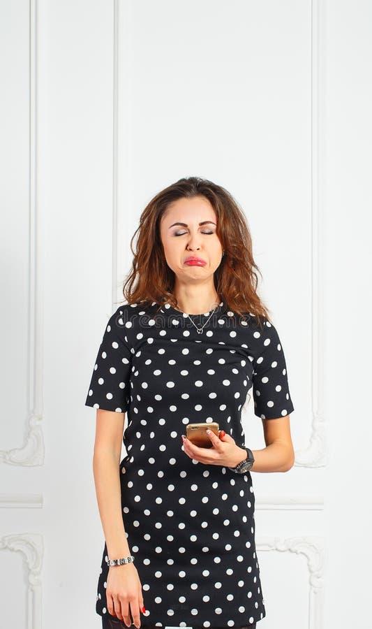 Una mujer joven hermosa que sostiene el teléfono muy trastornado imágenes de archivo libres de regalías