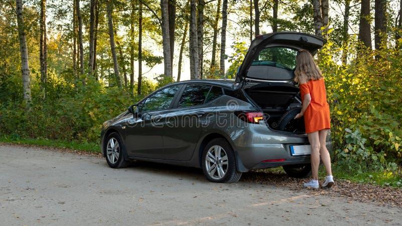 Una mujer joven hermosa quita la rueda de repuesto de la bota del coche imagen de archivo libre de regalías