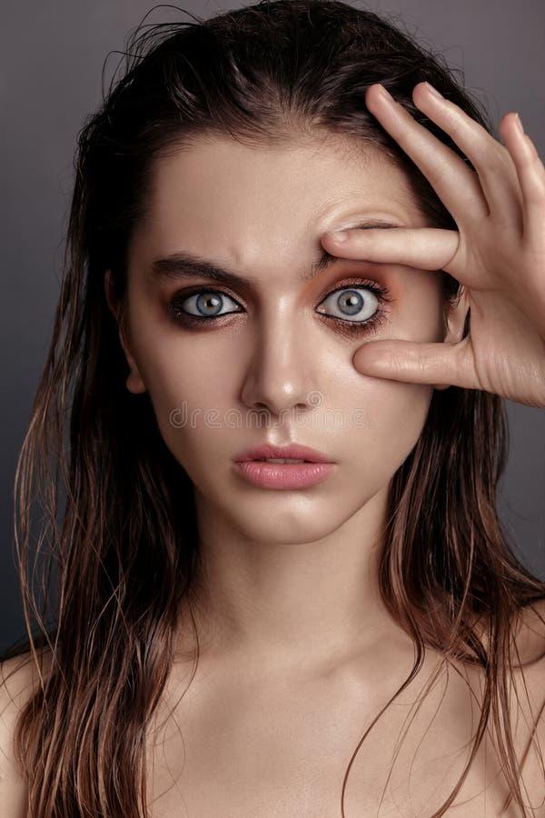 Una mujer joven la abre los ojos en estudio foto de archivo libre de regalías