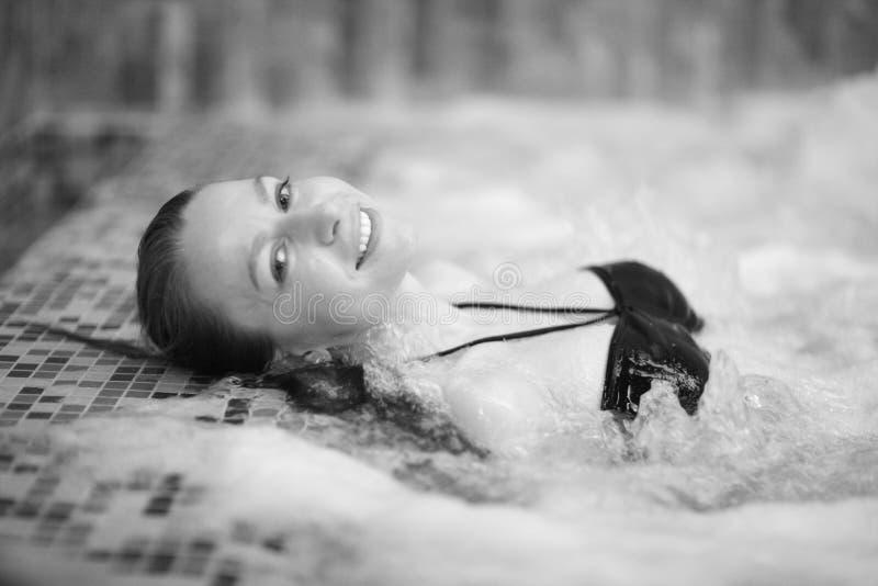 Una mujer joven mientras que nada en una piscina del balneario foto de archivo