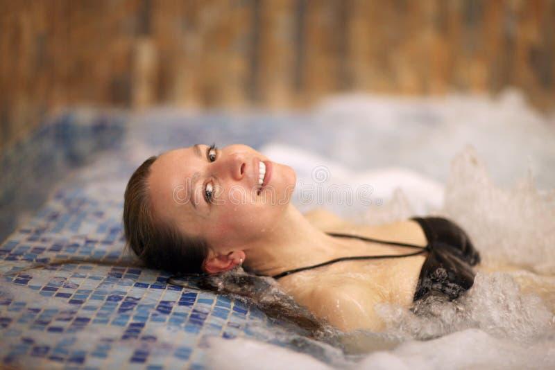 Una mujer joven mientras que nada en una piscina del balneario imágenes de archivo libres de regalías