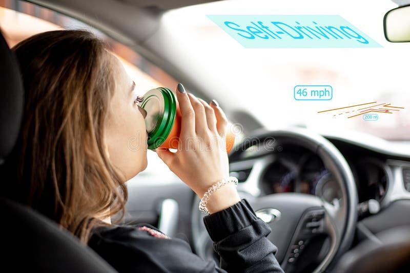 Una mujer joven monta en coche con café de conducción autónomo del modo y de las bebidas fotografía de archivo libre de regalías