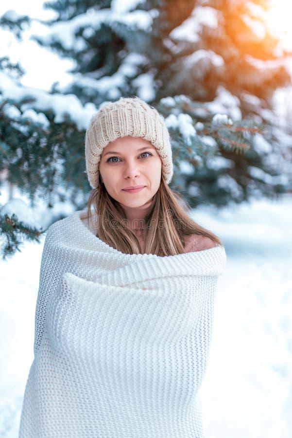 Una mujer joven, una muchacha hermosa en un sombrero blanco y la manta envuelta para arriba, calienta en el invierno en el bosque foto de archivo