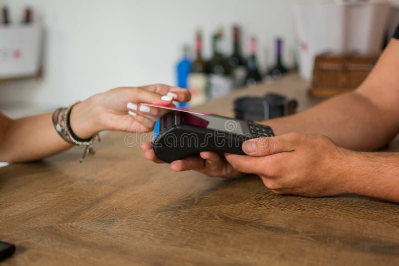 Una mujer joven paga con la tarjeta de crédito en un pub El camarero lleva a cabo un terminal de la tarjeta de crédito Cierre par foto de archivo